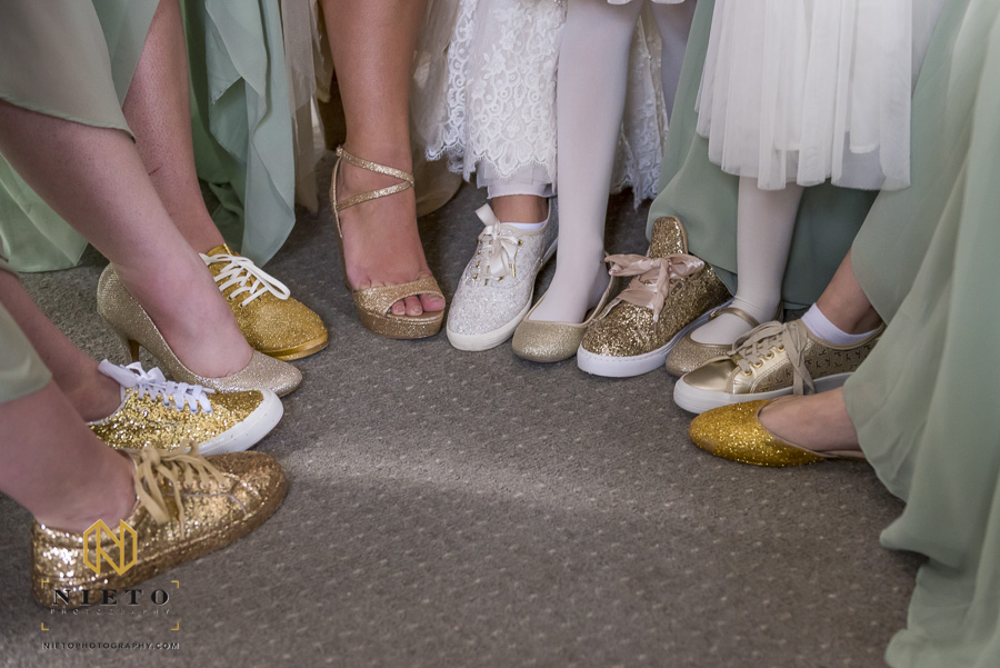 close up shot of the Brides white shoes and bridesmaids with their gold glitter shoes