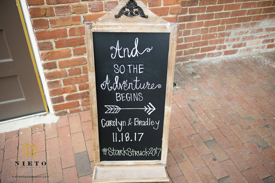 A chalk board sign pointing guest where to sit for the outdoor Market Hall wedding