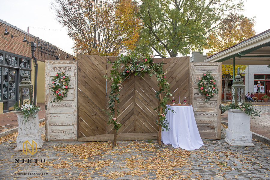 The floral decorated arbor with wooden door backdrop outside of Market Hall in downtown Raleigh