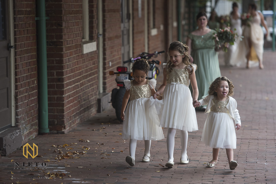 the flower girls walking together holding hands outside of Market Hall