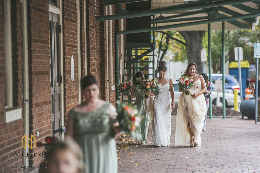 the bride and maid of honor walking together to line up for the ceremony