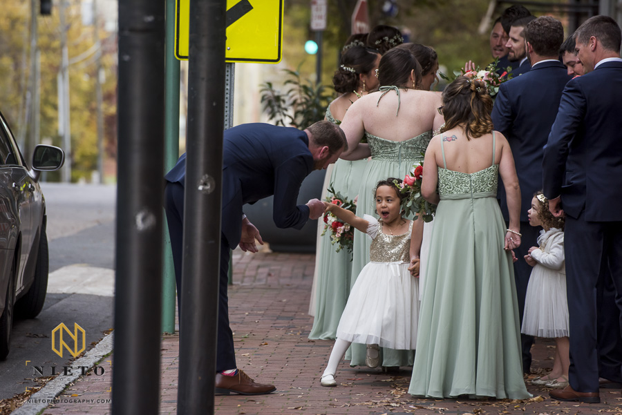 one of the flower girls playing with a groomsman before the wedding ceremony