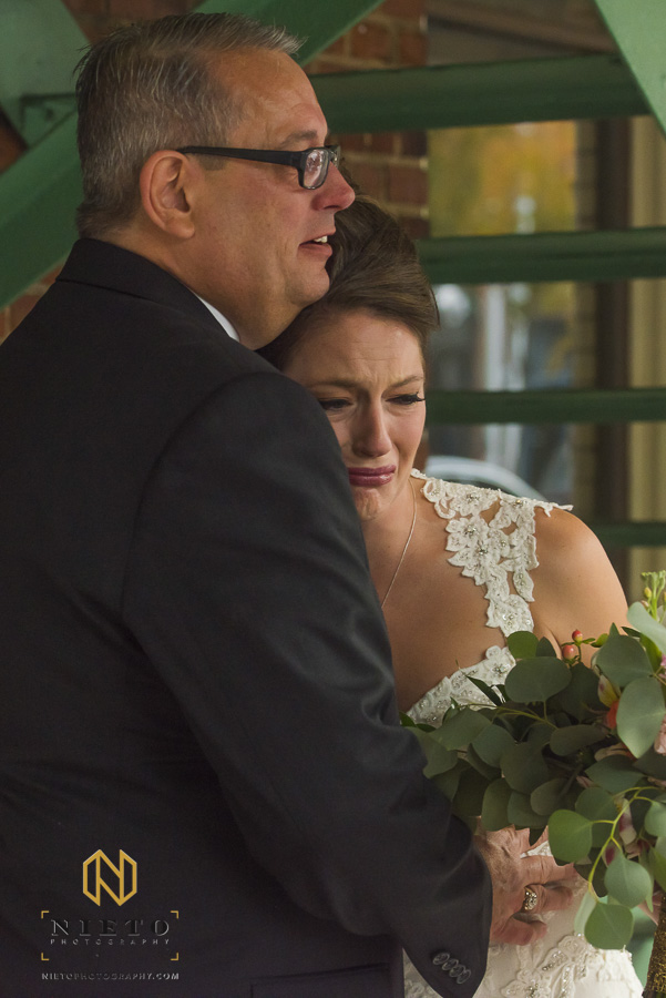 the father of the bride hugging his daughter as she cries before the wedding ceremony