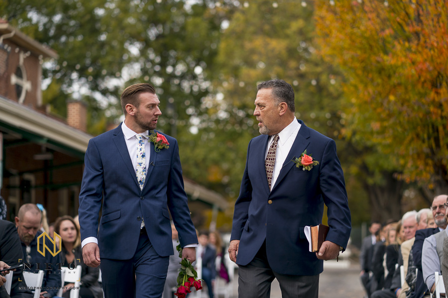 the wedding officiant and groom talking to each other as they walk to the altar