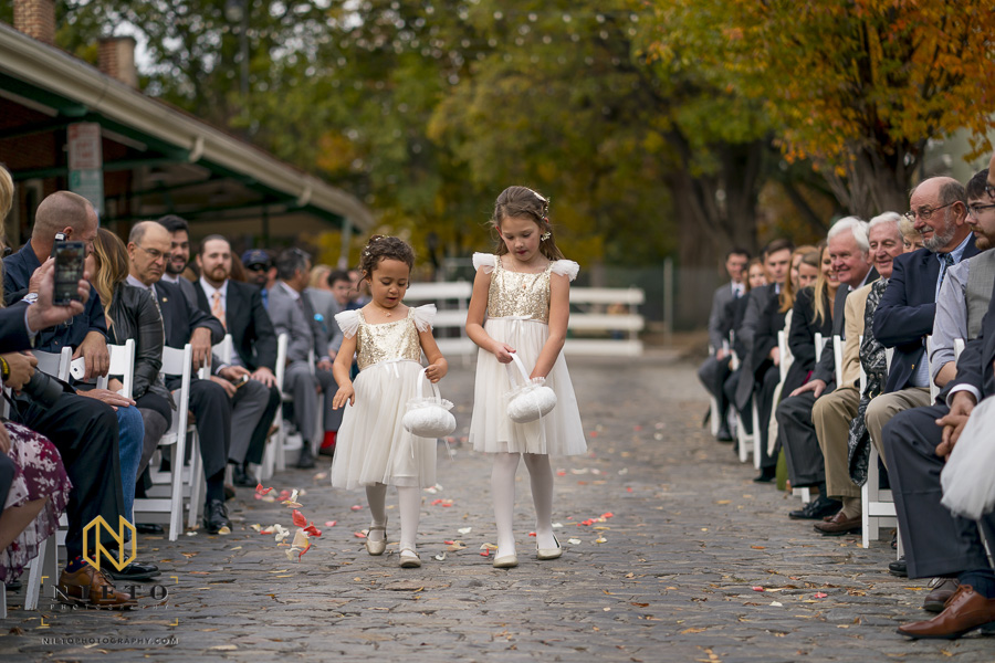 two flower girls walking down the aisle throwing the flowers out of their baskets