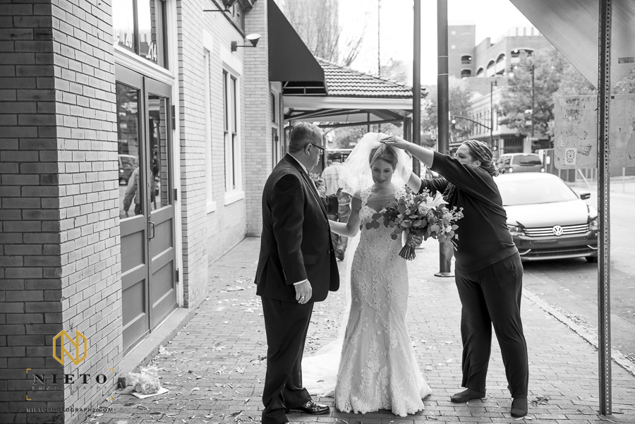 black and white image of the wedding planner adjusting the wedding veil before the bride walks down the aisle with her father
