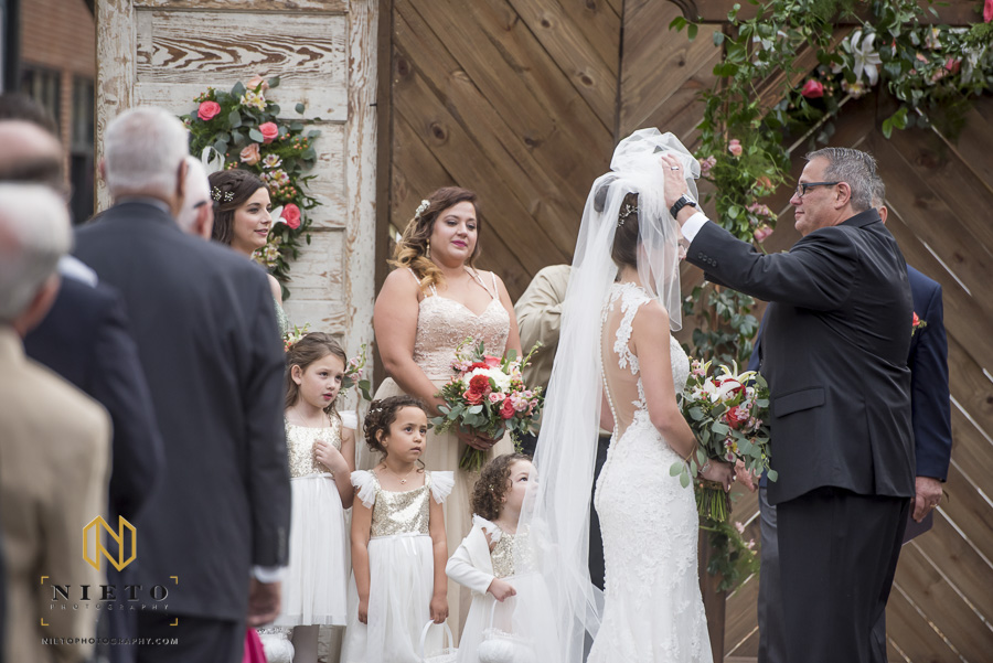 the father of the bride removing the brides face covering as the flower girls stare at her