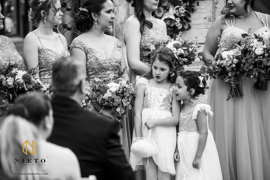 black and white image of the flower girls talking during the Market Hall wedding ceremony