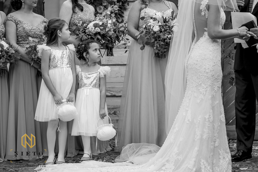 black and white image of the flower girls look at the bride and groom during the wedding ceremony outside at Market Hall