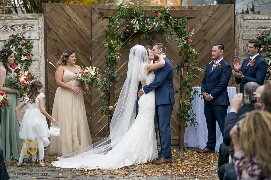 the bride and groom kissing for the first time at their Historic Market Hall wedding ceremony