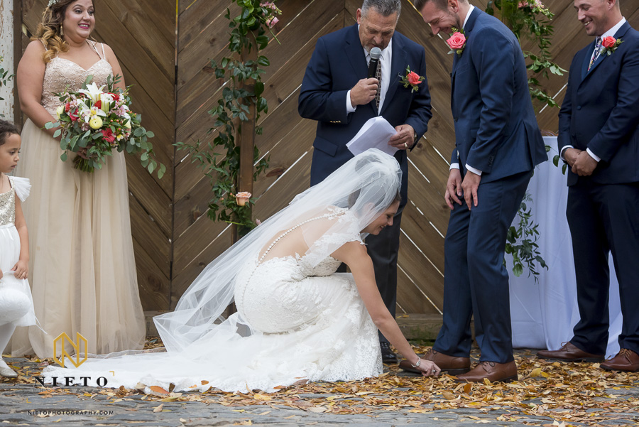 the bride bending down to pick up the grooms ring that she dropped during the ceremony