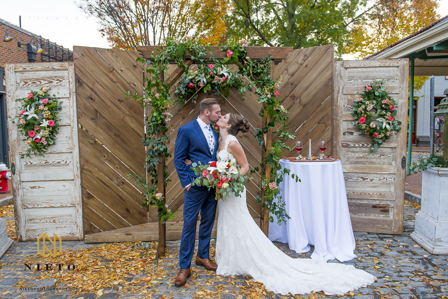 the bride and groom kissing in front of their arbor after their Market Hall wedding ceremony