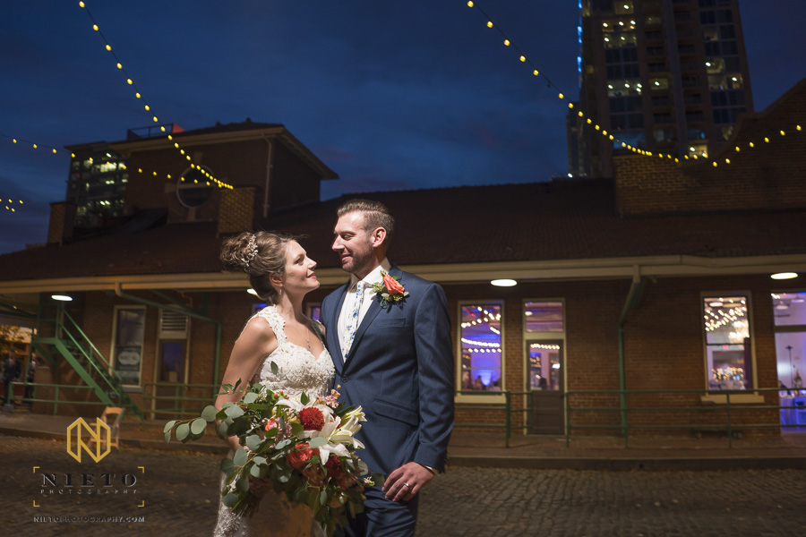 night time shot with a dark blue sky outside of Market Hall of the bride and groom looking at each other