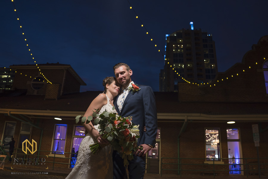 night time shot at Market Hall with bride and groom snuggling into each other