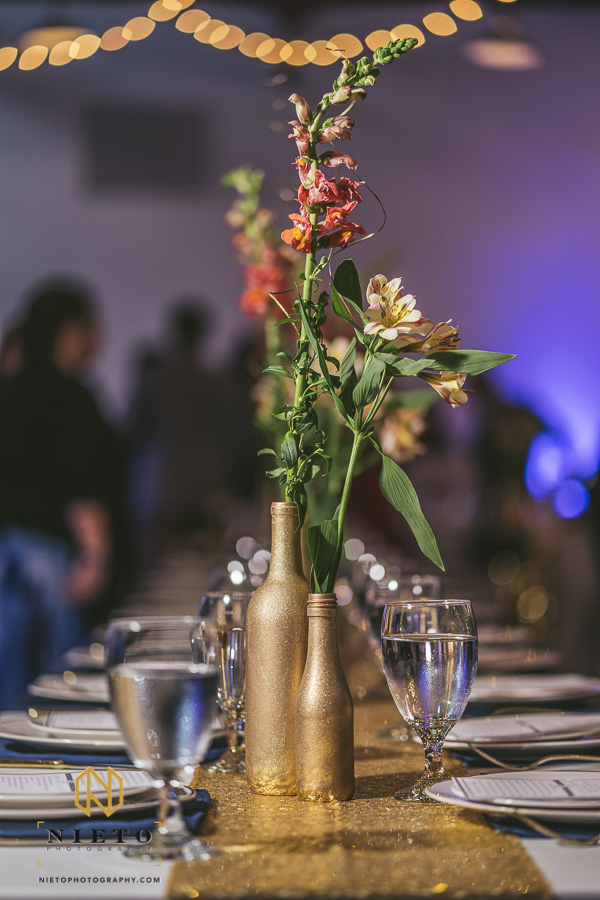 gold bottles as centerpieces with flowers in them