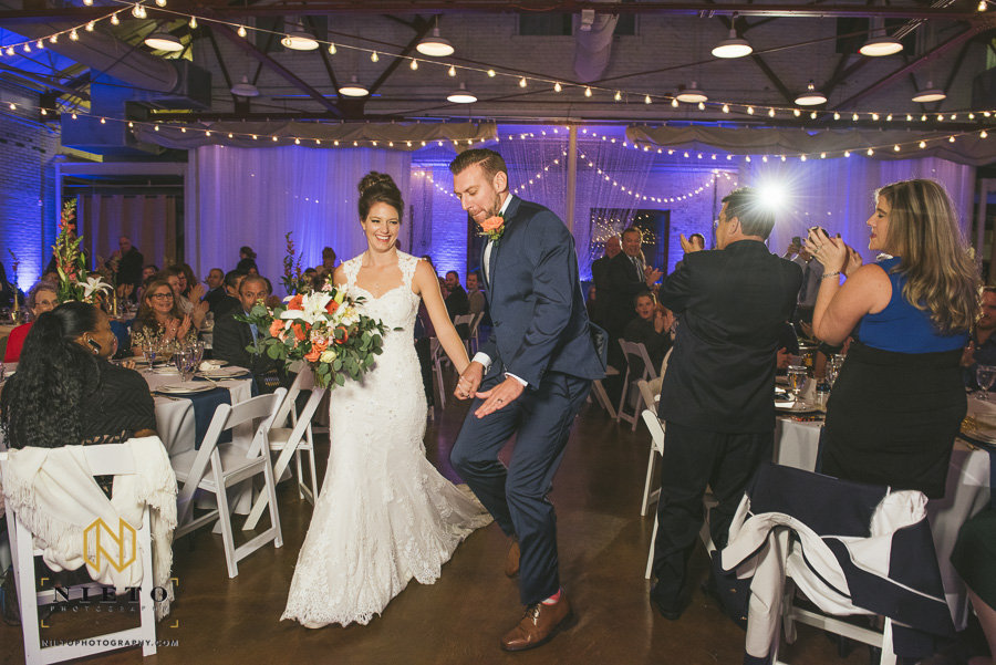 the bride laughing as the groom dances during his wedding introduction at Market Hall