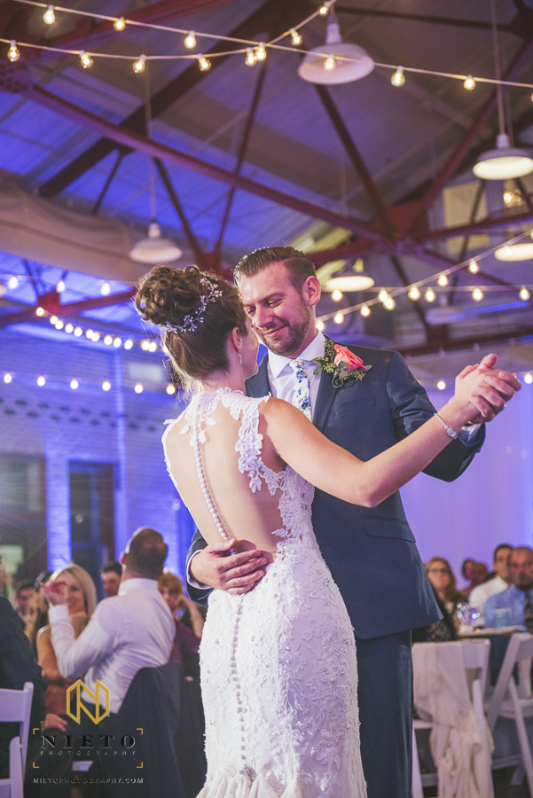 the groom smiling as he dances with the bride during their first dance