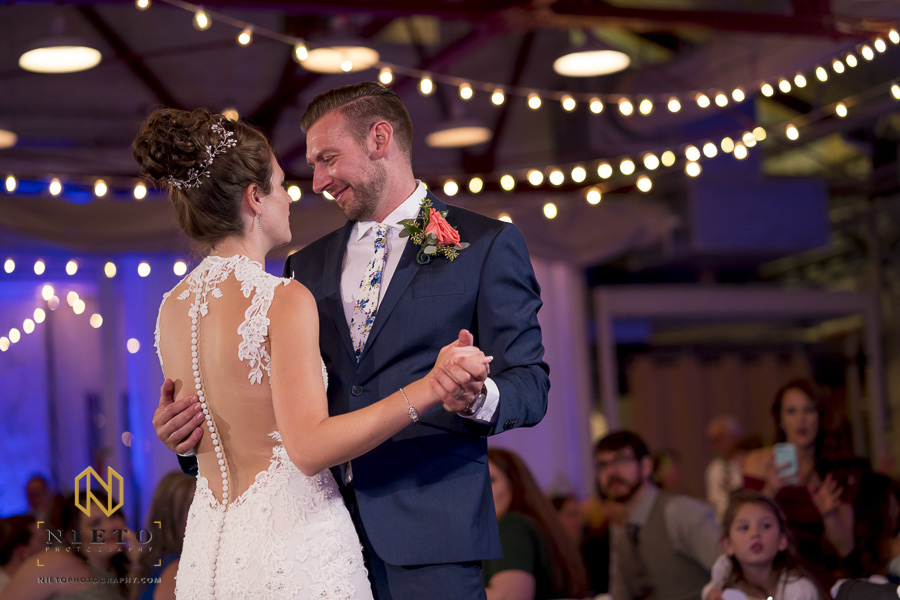 the groom smiling and dancing with the bride during their first dance together at Market Hall