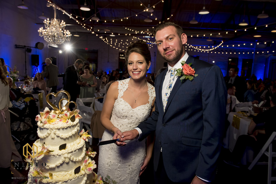 bride and groom posing together with a knife before cutting the cake at Market Hall