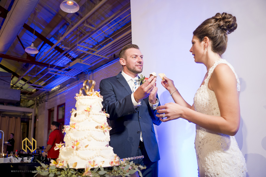 the bride and groom both holding pieces of cake in their hands before they feed each other