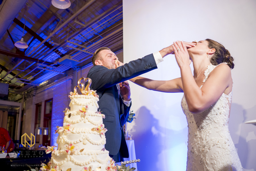 bride and groom smashing cake into each others face after their cake cutting