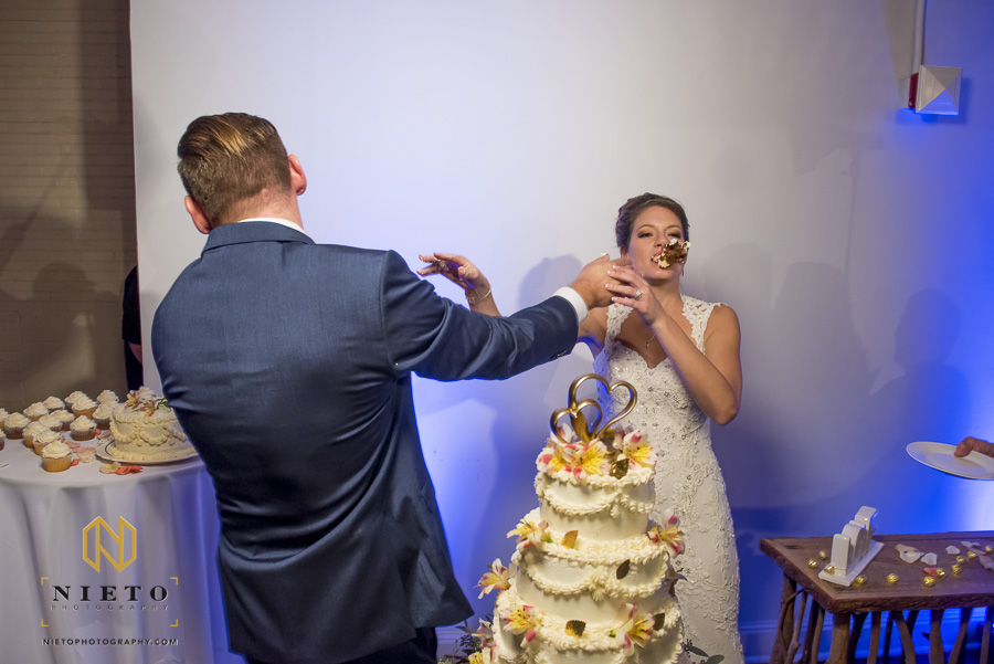 picture of the bride with cake stuck to her face as the grooms back is to the camera