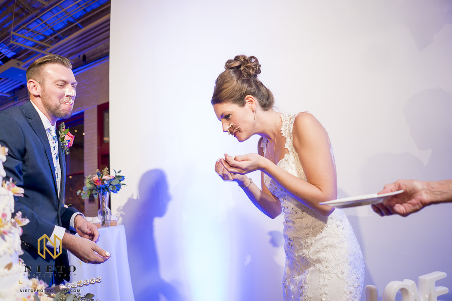 the groom with cake on his face as the bride tries to get the cake of her own face
