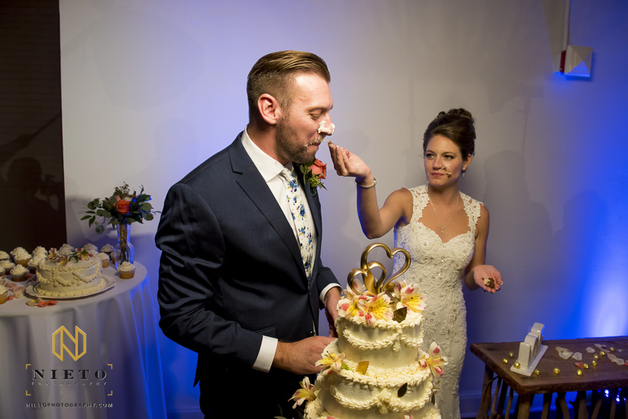 the bride trying to take some cake off the grooms nose at Market Hall
