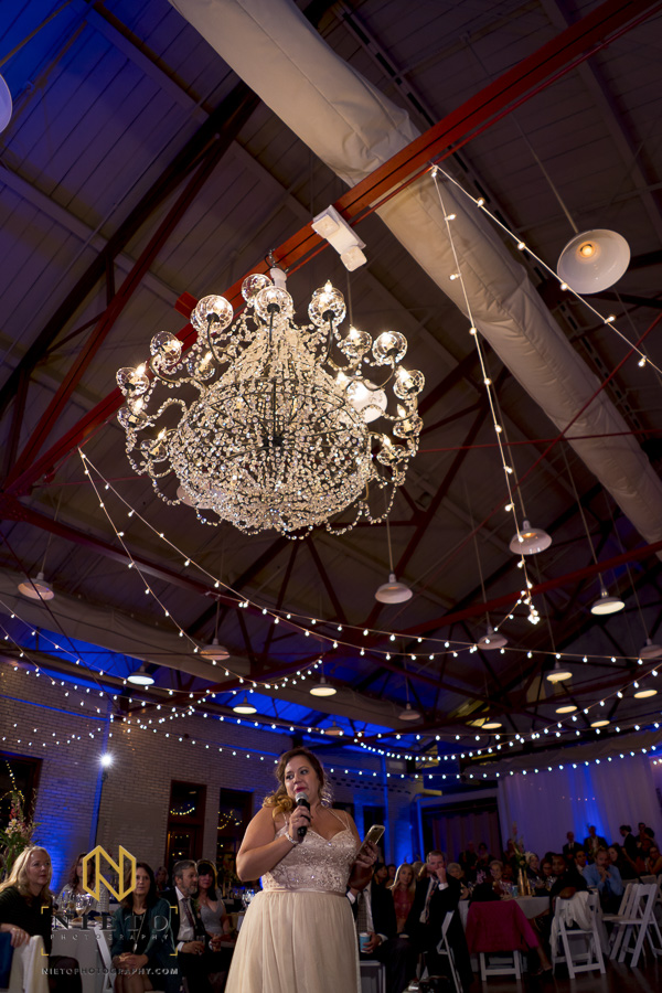maid of honor giving toast under the chandelier from Themeworks Creative at Market Hall