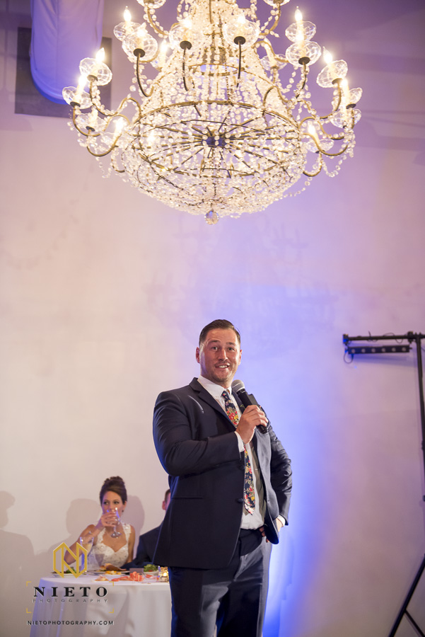 The best man giving his toast under the chandelier provided by Themeworks Creative at Market Hall