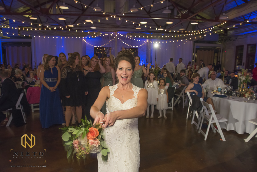 the bride about the throw her bouquet as the single ladies stand behind her