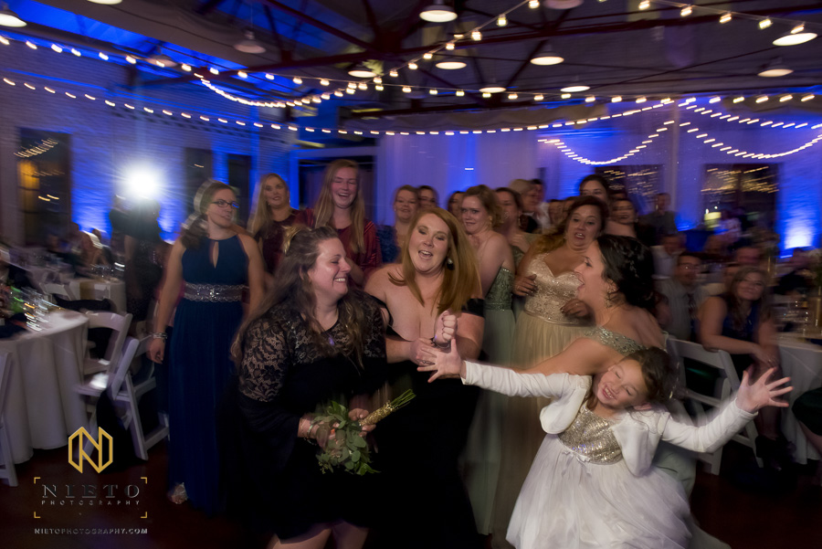 women fighting over the brides bouquet pushing down a flower girl