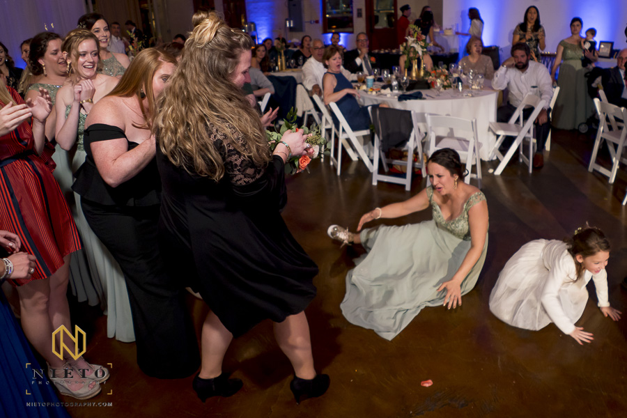 bridesmaid falling on the ground as two other women fight over the brides bouquet