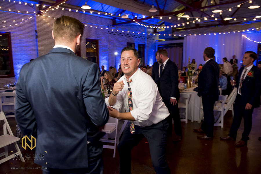 groomsman rolling up his sleeves in preparation for the garter toss