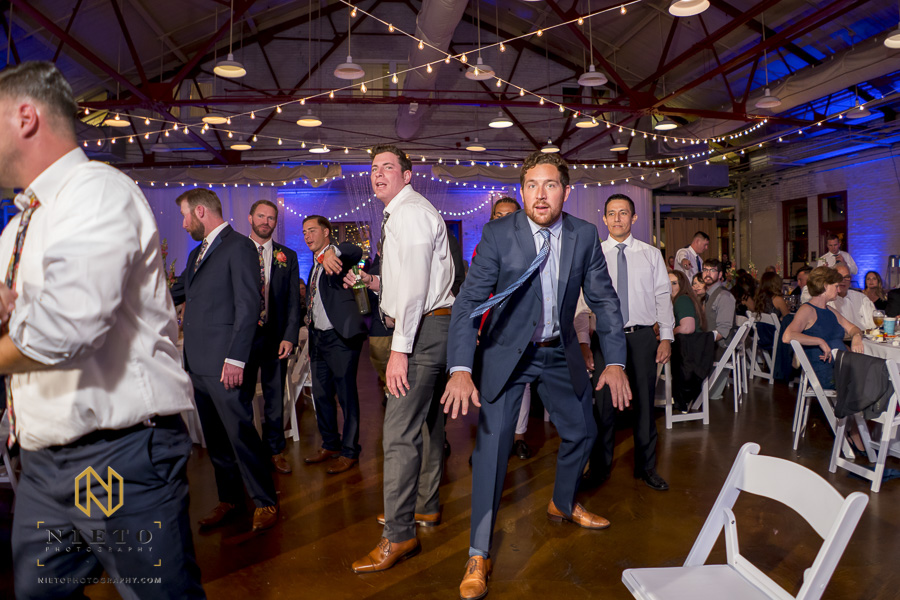 two single male wedding guest stretching before the garter toss