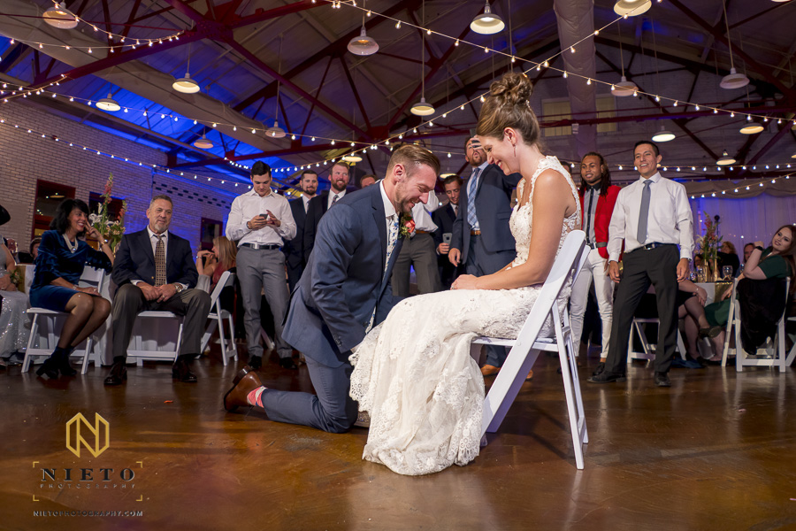 the groom removing the garter from the brides leg with the single male wedding guest waiting patiently