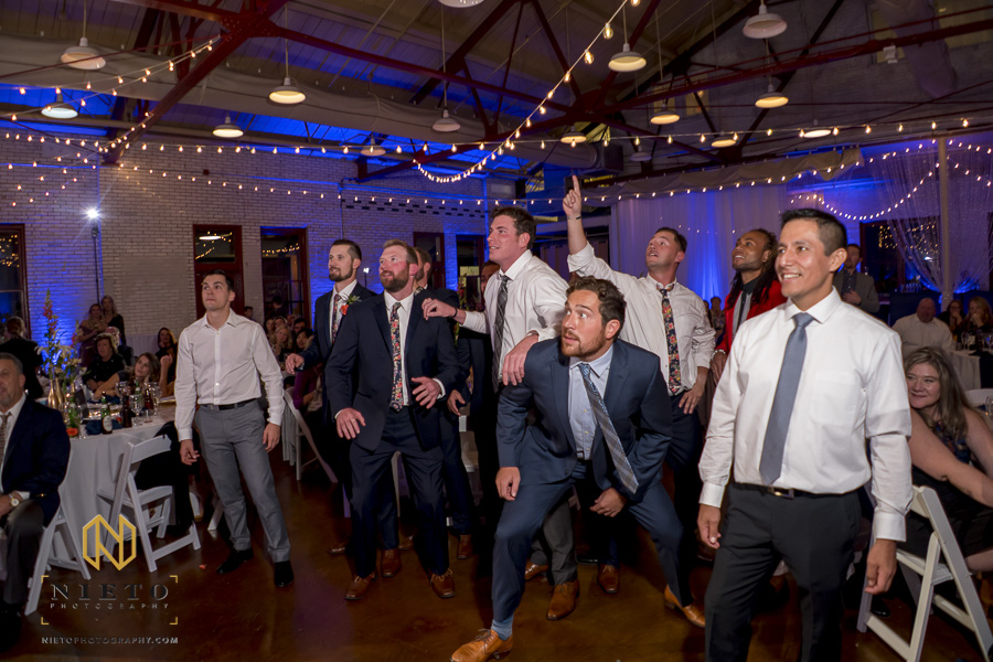 male wedding guest getting ready to jump to catch the garter