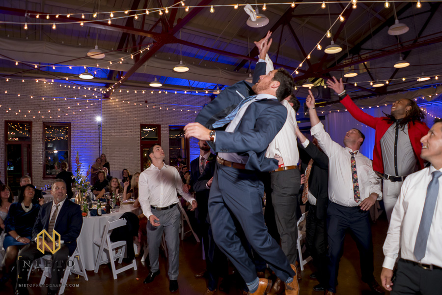 male guest jumping to try and catch the garter at Market Hall