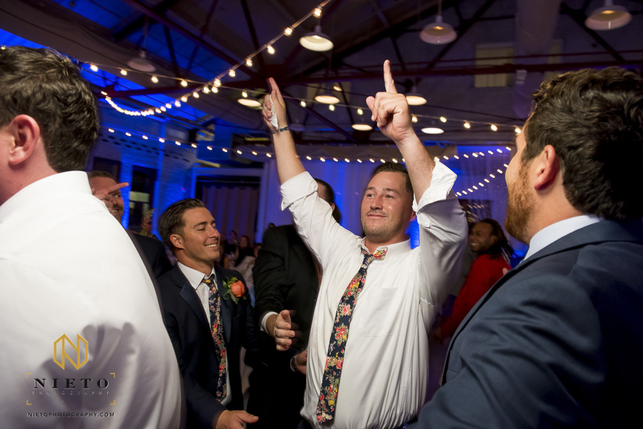 groomsman raising his hands in victory after he caught the garter
