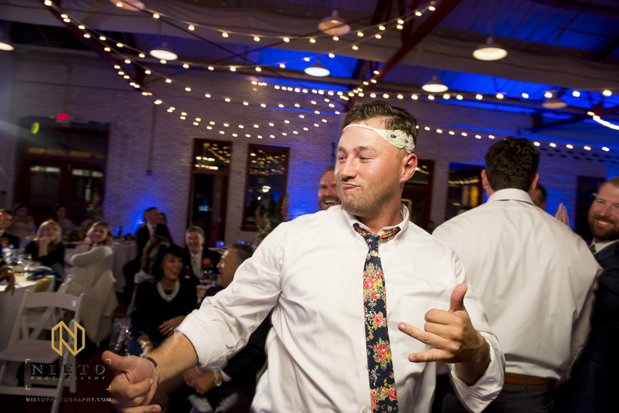 groomsman dancing and wearing the garter around his head