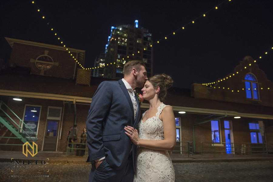 groom kissing his bride on the forehead outside of Market Hall at night with downtown raleigh in the background