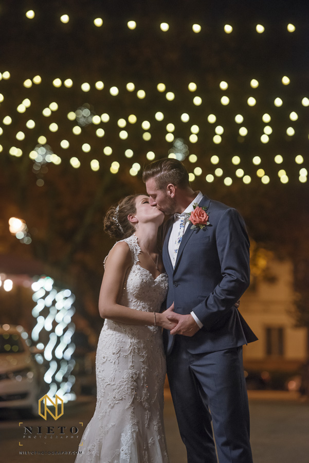 night portrait of the bride and groom kissing under string lights outside their Market Hall wedding