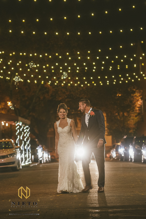 groom and bride walking and holding hands at night under the string lights outside of Market Hall