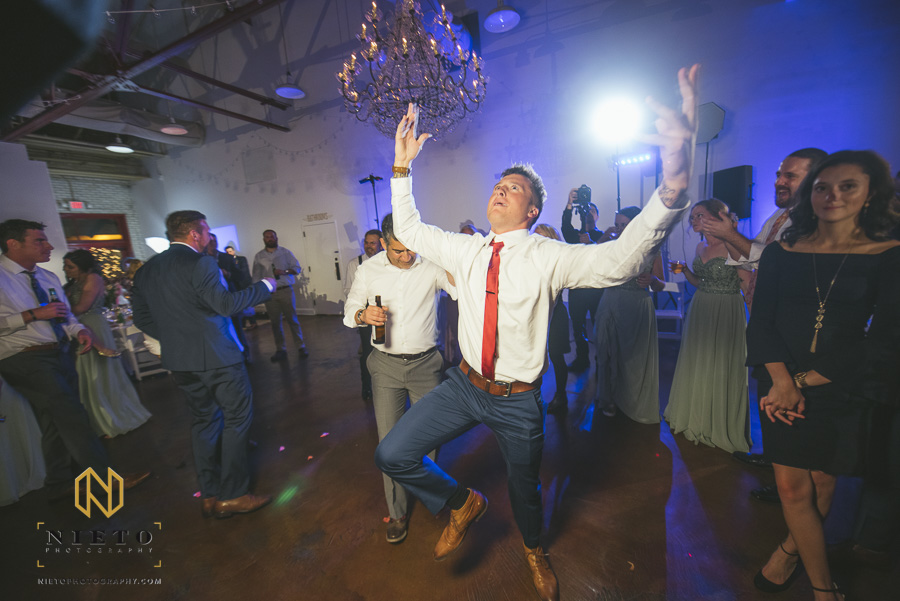 wedding guest with a red neck tie dancing by himself at Market Hall