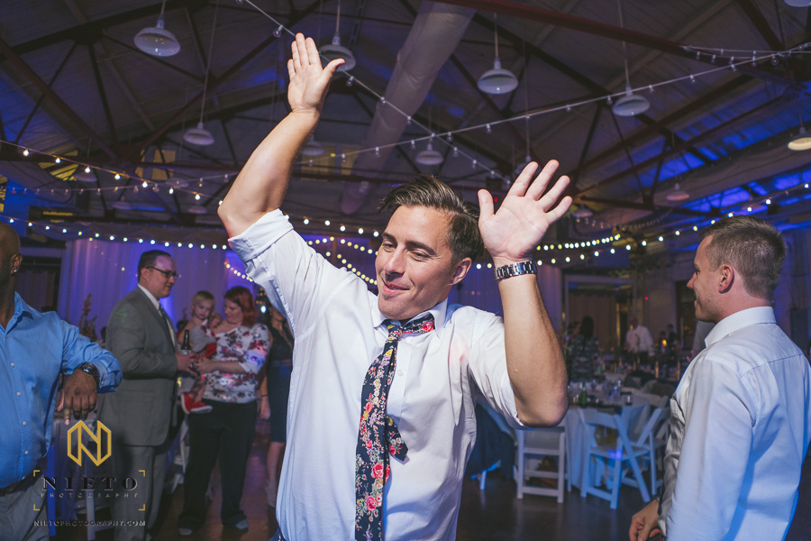 groomsman dancing by himself with his hands in the air at Market Hall