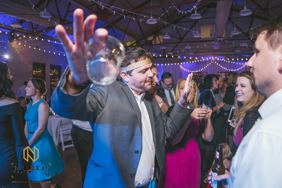 wedding guest dancing with a neck tie around his neck