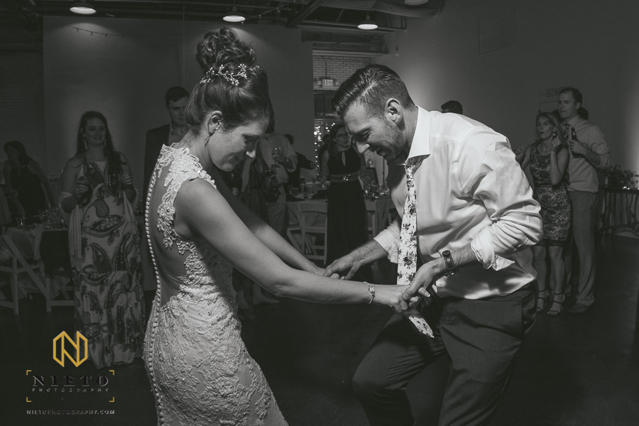 black and white picture of bride and groom holding hands together dancing