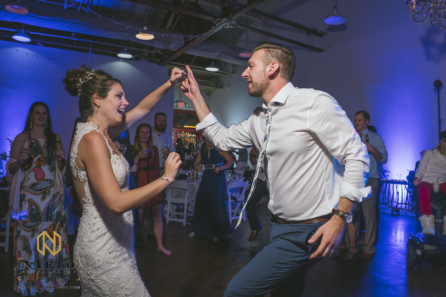 bride and groom dancing together hold hands and smiling