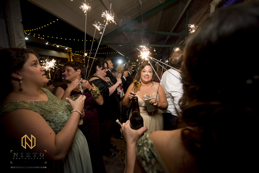 bridesmaids lighting sparklers together outside of Market Hall