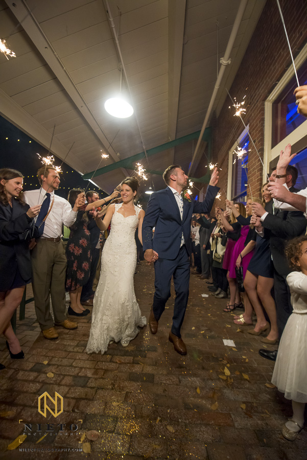 the bride and groom holding hands walking by their guest during the sparkler exit at Market Hall
